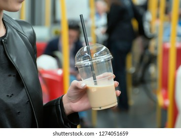 Young girl holding disposable coffee cup in train