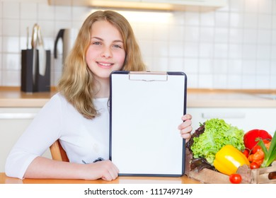 young girl holding a empty placard beside a box full of vegetables