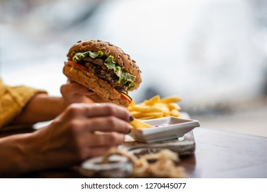 Young girl holding fast food burger, american meal. Tasty grilled made burger with beef, tomato, cheese, cucumber and lettuce. Mockup space for text message or design.