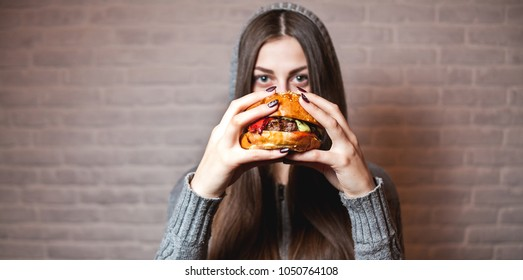 Young girl holding in female hands fast food burger, american unhealthy calories meal on background, hungry person smiling with grilled hamburger