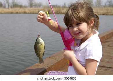 A young girl holding a fish she just caught