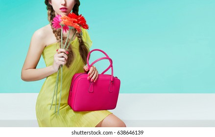 Young  girl holding flowers and pink leather purse. sitting on the white bench with light light blue wall. Spring fashion image.