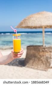 Junge Mädchen, die ein Glas Saft am türkisblauen Strand halten