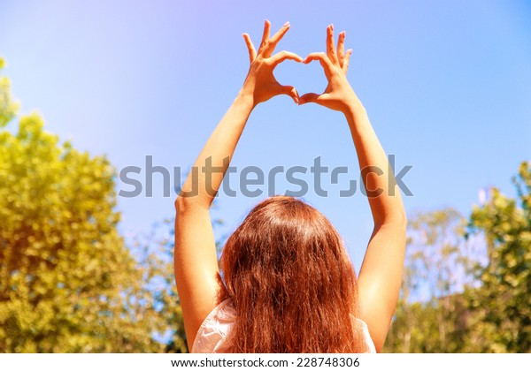 Young girl holding hands in heart shape framing on blue sky background