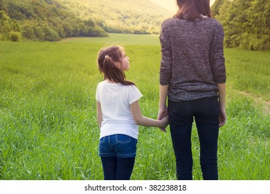 A young girl holding hands with her younger sister