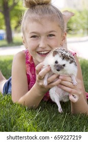 A young girl holding a hedgehog outside laying in the grass