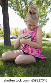 A young girl holding a hedgehog outside sitting in the grass