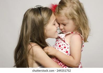 Young girl holding in her arms and kissing and having fun with her small sister. Girl trying to make her small upset sister smile