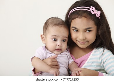 young girl holding her baby sister closely