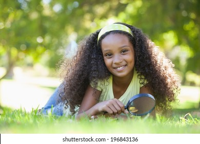 Young girl holding magnifying glass in the park smiling at camera on a sunny day