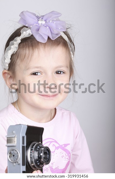 Young girl holding an old vintage camera