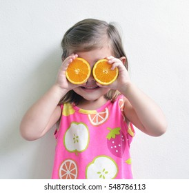 Young girl holding oranges slices over eyes