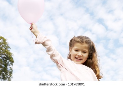 Young girl holding pink balloons against a blue sky and smiling in the park.