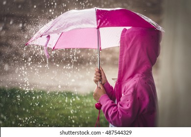 A young girl is holding a pink umbrella in a massive rain storm.