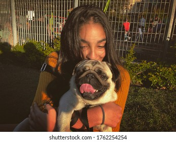 A young girl holding a pug dog with her hands. Close spot.