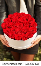Young girl holding red roses in white gift box