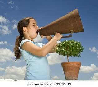young girl holding and small tree and shouting with a megaphone against blue sky