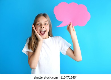 Young girl holding speech bubble on blue background