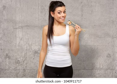 Young girl Holding Sushi Roll with chopsticks, indoor