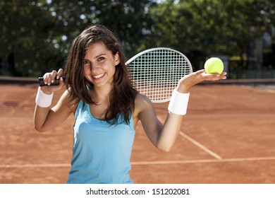 Young girl holding tennis ball on red court