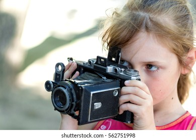young girl holding a video camera and shoots video
