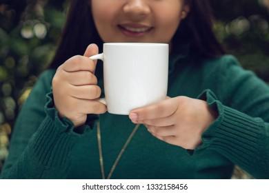 Young girl holding a white mug