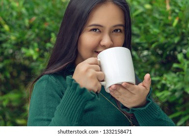 Young girl holding a white mug having a zip