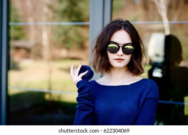 Young girl holding woolen brooch on terrace. Wearing blue woolen sweater and sunglasses