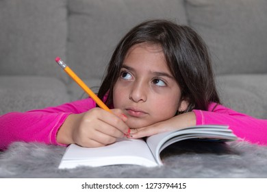 A young girl holding a yellow pencil is thinking while doing her homework
