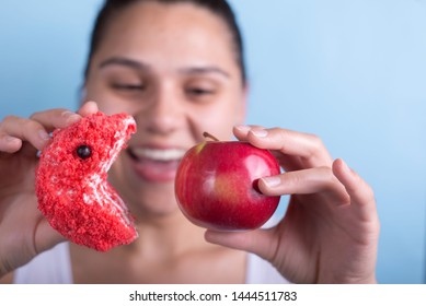 A young girl holds a cake and an apple in her hand, plays with them, the cake tries to eat an apple. Concept of junk food vs healthy