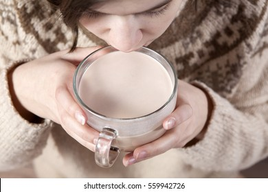 Young girl  holds cocoa. Face in un focus