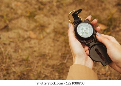 A young girl holds a compass. The concept of travel and adventure. Search for directions. copy space.