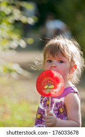 A young girl holds a giant lollipop outside.