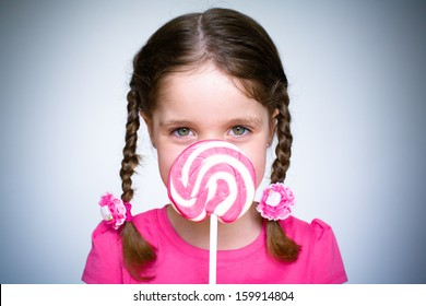 A young girl holds a large spiral lollypop whilst dressed in pink.