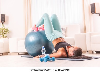 Young girl holds legs on a fitness ball lifting her whole body with elbows on the floor. Home workout using a mat, dumbbells and a swiss ball.