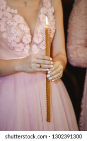 A young girl holds a lit candle in the church.