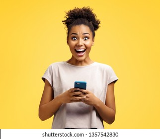 Young girl holds phone, happy to receive notification. Photo of african american girl wears casual outfit on yellow background. Emotions and pleasant feelings concept.
