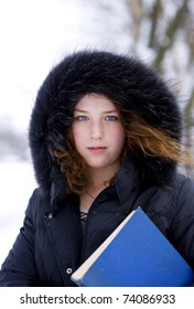 Young girl in hood with blue book