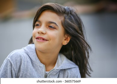 Young girl with a hooded sweatshirt on outside. Natural light.