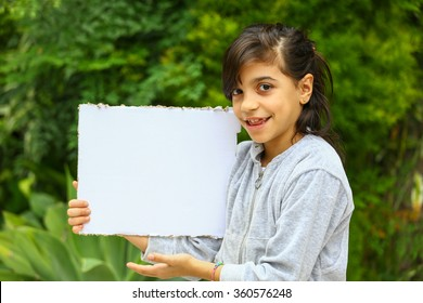 Young girl with a hooded sweatshirt on outside. Holding a copy space sign.