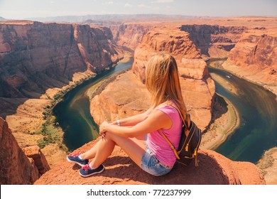 Young girl at the Horse shoe bend in the USA. Successful model on the edge of the cliff. Happy life.