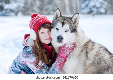 Young girl hugging a dog Husky winter