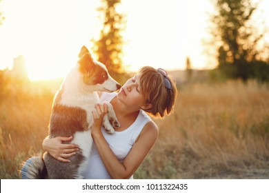 A young girl hugs a dog. Portrait at sunset in the park.