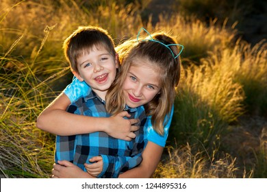 A young girl hugs her little brother from behind for a portrait in late afternoon, backlit light.  They are both blond and wearing blue with blue eyes.  The boy has Ptosis.