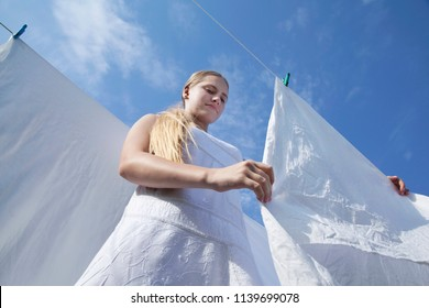 Young girl is hung up sheets on clothesline. Drying clean laundry in rope outdoors on sunny day. Teenager in white dress on blue sky background