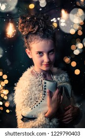 young girl with ice skates in a winter evening
