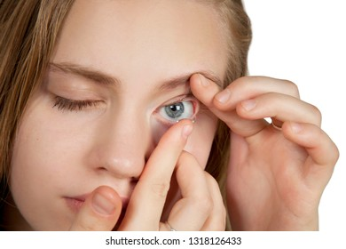 A young girl inserts contact lenses into her eyes. On a white background. Close-up. Looking into the camera.