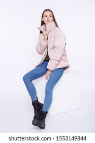 Young girl in a jasmine down jacket sitting on a white cube isolated on a white background.