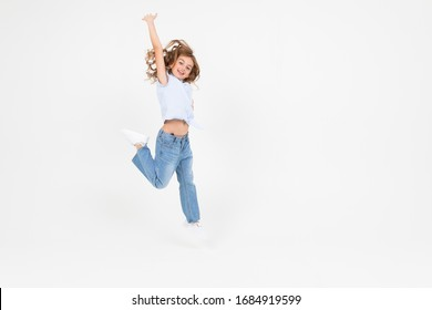 young girl in jeans jumping with happiness on a white background with copy space