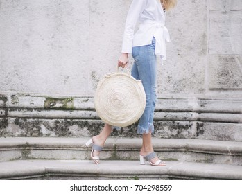 A young girl in jeans and a large handbag in her arms. Fall of fashionable street clothes. Styl everyday - Shutterstock ID 704298559
